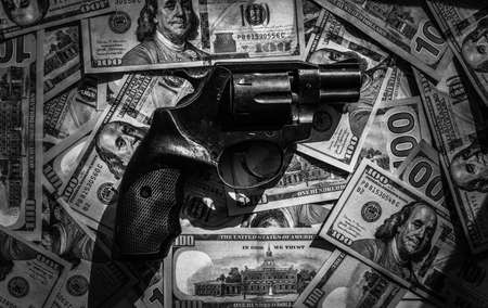 The revolver lies on one hundred dollar bills close up