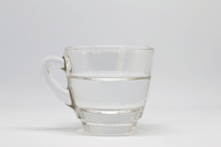 housewares: half a glass of water on white background