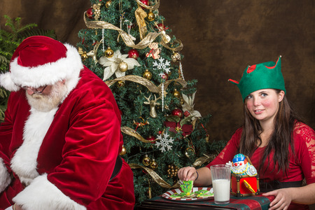 Elf stealing cookies from Santa Claus photo