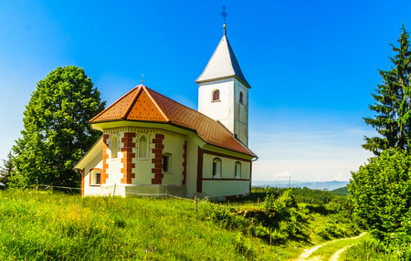 View on small church of Cerkev sv. Ahaca by kamnik in the mountains of Slovenia Stock Photo - 108521597