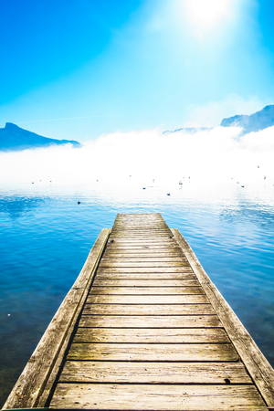 View on morning fog on Pier of lake Mondsee and Alps in Austria Imagens