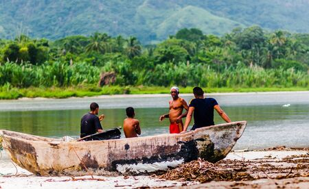 Palomino, Colombia on 20th November 2014: View on Group of people waiting by wooden boat on the beach of Palomino next to Tayrona national park 免版税图像 - 142308211