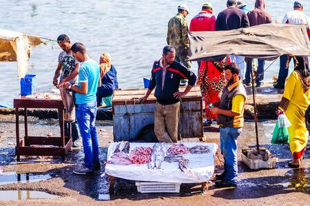 Essaouira, Morocco - November 05, 2015: View on group of Fishermen selling fresh fish on the market in the old port of the town 新闻类图片