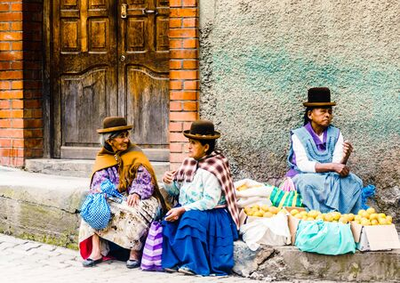 Coroico, Bolivia on 3rd May 2017: View on group of indigenous woman selling local products on market