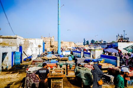 Essaouira, Morocco - November 05, 2015: View on group of Fishermen selling fresh fish on the market in the old port of the town 免版税图像 - 142308217