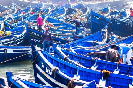 Essaouira, Morocco - November 05, 2015: View on blue wooden rowing boats at the and fisher man in the port of Essaouira in Morocco