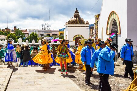 Cocacabana, Bolivia 30th April 2017: View on group of local people celebrating parade and playing drum and woman in dress dancing