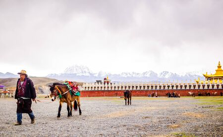 Tagong Temple on the Tagong Grassland in Ganzi Prefecture, Sichuan Province on 12th May 2015 - View on temple and npmadtd with horses