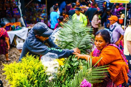 Chichicastenango, Guatemala on 2th May 2016: View on Indigneous woman with colorful clothes selling flowers on market in Chichicatenango 新闻类图片