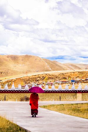 Tagong, China on 12th May 2015 - View on Tibetan monk walking with umrella 免版税图像 - 142308261
