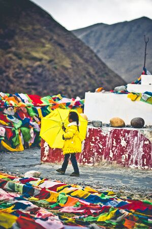 Tagong, China on 12th May 2015 - View on girl with yellow umbrella going arround tibetan stupa