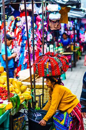 Chichicastenango, Guatemala on 2th May 2016 - View of Indingenous maya woman carry products on the top of her head on local maya market