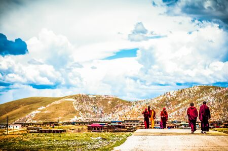 Tagong, China on 12th May 2015 - View on group of tibetan monks walking in mountain landscape