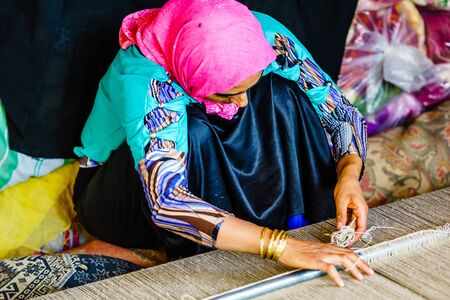 Shiraz, Iran on October 25th 2016, View on woman weaving carpet 新闻类图片