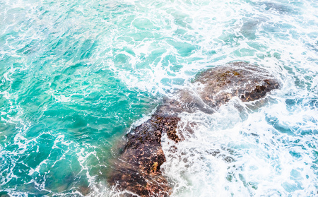 View on Texture of Turquoise sea with spray on stones