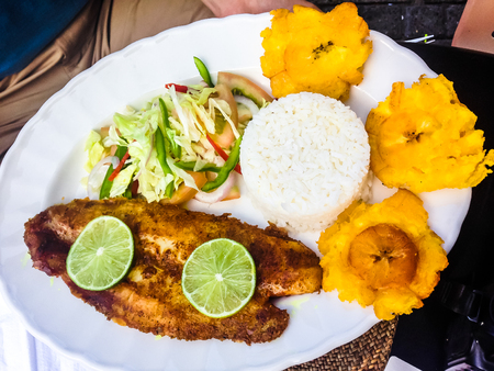 Fish, rice, bananas and a salad. Meal on Carribean coast of Colombia Stock Photo