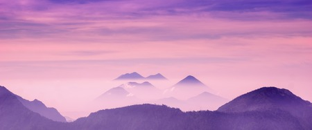 Skyscape of cold purple mountains with mist and fog close to Quetzaltenango Stock Photo