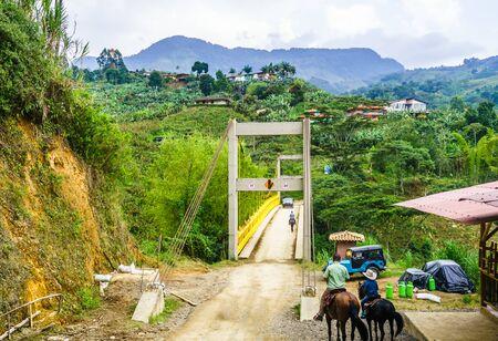 Peope doing horse trekking next to yellow bridge next to Jardin in Colombia