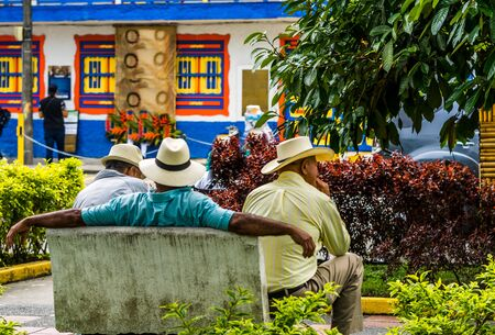 View on people of Colombia, group of old man sitting on bench in the colorful streets of Filandia Village Stock Photo