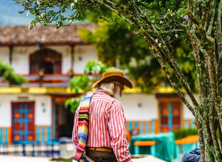 View on man wearing a sombrero and folded poncho over the shoulder in colonial village of Jardin, Colombia