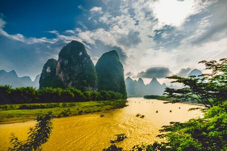 Boats on Li River in Yangshuo China surrounded by Karst Mountains