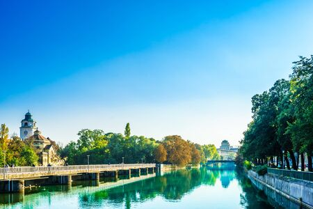 View on Colorful autumn landscape in front of Mueller Volksbad of Isar river - Munich