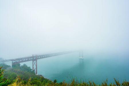 Fog at the Ponte 25 de Abril is a suspension bridge across the river Tejo, Portugal 免版税图像