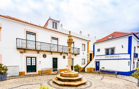 Streets of Ericeira, traditional white houses with blue stripes, Portugal 免版税图像