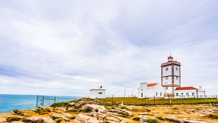 Lighthouse on Cabo Carvoeiro and Atlantic ocean next to Peniche, Portugal 免版税图像 - 142126569