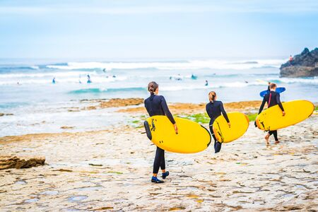 Group of surfer at the beach of Ribeira d'Ilhas next to Ericeira, Portugal