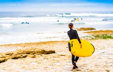 Surfer girl next to Ericeira at beach Ribeira D'ilhas, Portugal