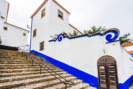Narrow White Blue Street in Mediieval City Obidos Portugal 免版税图像 - 142126210
