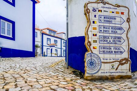 Streets of Ericeira, traditional white houses with blue stripes, Portugal 免版税图像 - 142154200
