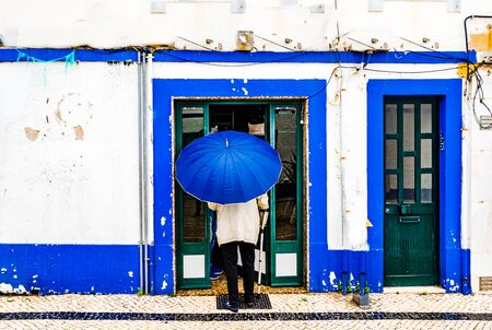 View on Old man with umbrella in front of blue colored building in the city of Ericeira, Portugal