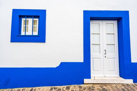 Traditional white houses with blue stripes, Portugal 免版税图像 - 142154204