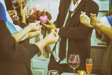 Girl smiled excitedly as businessman gave flowers and a heart-shaped symbol, Among group of friends at party congratulated mini heart, With vintage color scheme