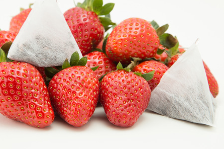 A pile of strawberries isolated over white background with tea bags on top photo