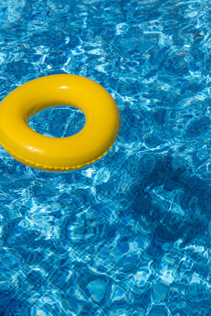 Yellow pool float, pool ring in cool blue refreshing swimming pool Stock Photo