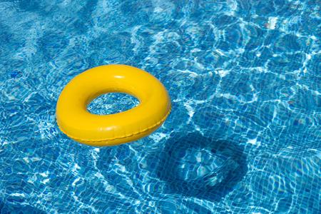 Gele pool float, zwembad ring in koele blauwe verfrissende zwembad