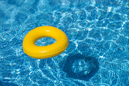 house float on water: Yellow pool float, pool ring in cool blue refreshing swimming pool Stock Photo