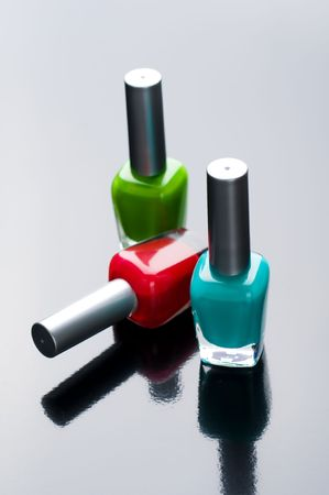 Nail polish bottles on gloss background Stock Photo