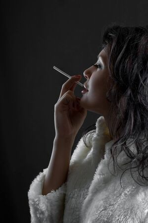 beautiful brunette girl with cigarette in hand photo
