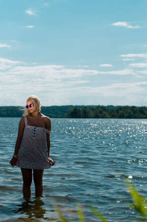 blond girl standing in river in sunglasses Stock Photo - 8261576