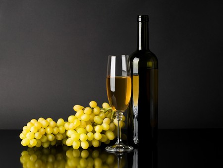 Bottle and glass of white wine with grapes against dark background Stock Photo