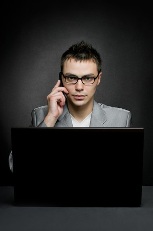 businessman with laptop and mobile phone on black Stock Photo - 8261118