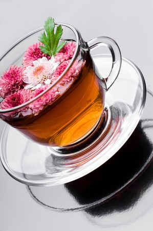 cup of herbal tea with flowers on black