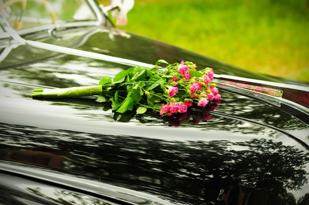 cowl: Pink wedding bouquet on cowl of  black car Stock Photo