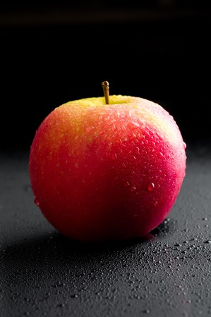Red apple with water drops over black