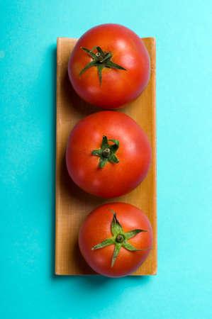 ripe tomatoes on blue background Stock Photo