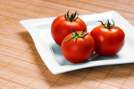 ripe tomatoes on plate on wooden background Stock Photo